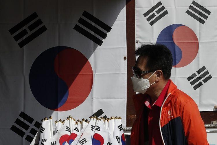 Seorang pria yang memakai masker wajah berjalan di dekat bendera nasional yang dipajang di toko suvenir di Imjingak Pavilion di Paju, Korea Selatan, Minggu, 11 Oktober 2020.