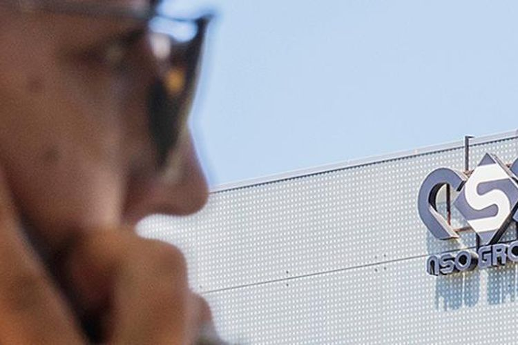 Seorang perempuan menggunakan iPhone di depan kantor perusahaan Israel penyedia perangkat pengintaian, NSO Group, di kota Herzliya, dekat Tel Aviv, Israel, Minggu (28/8). Dengan kemampuan teknologi paling canggih dalam industri pengintaian di dunia yang mereka ciptakan, perusahaan-perusahaan Israel memasok peralatan militer dan polisi rahasia di sejumlah negara.