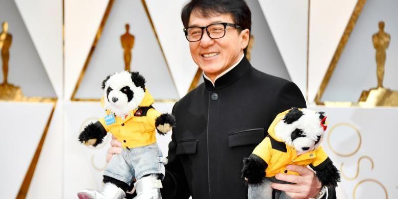 Aktor Jackie Chan membawa dua boneka panda ketika berjalan di karpet merah Academy Awards ke-89 di Hollywood & Highland Center, Hollywood California, Minggu (26/2/2017).