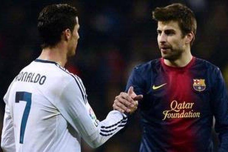Bintang Real Madrid dari Portugal, Cristiano Ronaldo (kiri), berjabat tangan dengan bek Barcelona dari Spanyol, Gerard Pique, seusai laga semifinal pertama Copa del Rey di Stadion Santiago Bernabeu, Rabu (30/1/2013). Pertandingan itu berakhir 1-1. Jutaan pengikut Ronaldo memberi ucapan selamat ulang tahun, Rabu (5/2/2013).