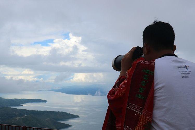 Pengunjung sedang menikmati pemandangan Danau Toba dengan teropong bintang di Huta Ginjang di Kabupaten Tapanuli Utara