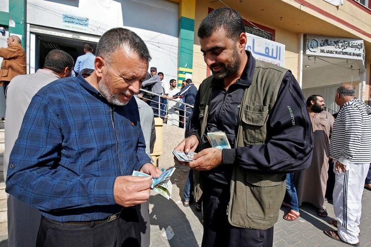 Pegawai Hamas menukar uang setelah mereka menerima gaji pertama sejak berbulan-bulan pada November lalu.