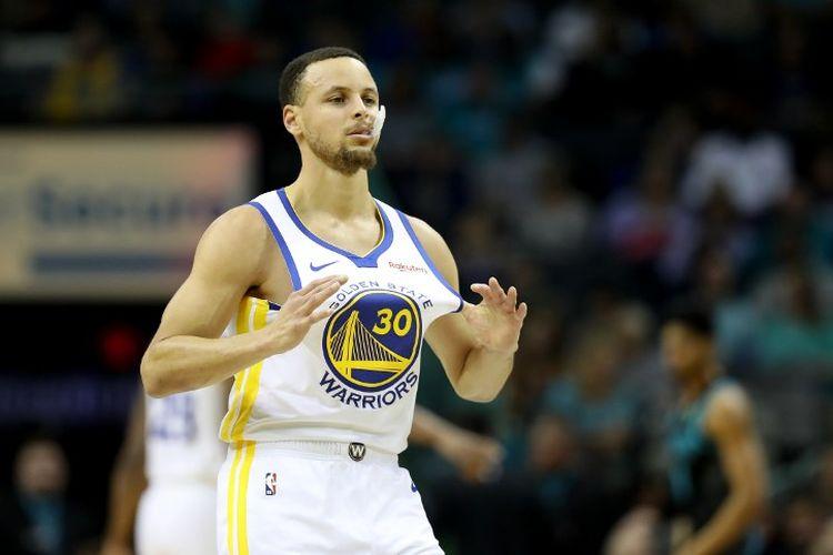 Bintang Golden State Warriors, Stephen Curry, memegang jersey-nya saat laga melawan Charlotte Hornets di Spectrum Center, 25 Februari 2019.