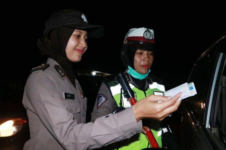 Polisi wanita dari Polres Aceh Utara memeriksa surat kendaraan bermotor di Kompleks Terminal Lhoksukon, Kabupaten Aceh Utara, Sabtu (29/12/2018) malam.
