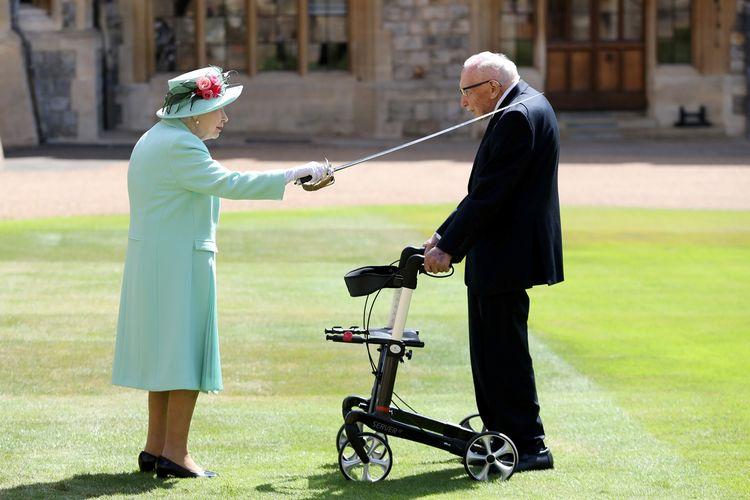 Ratu Elizabeth II menempatkan pedang kepada Kapten Tom Moore, sebagai tanda pemberian gelar bangsawan kepada pensiunan perwira berusia 100 tahun itu atas jasanya dalam mengumpulkan donasi bagi garda kesehatan Inggris selama Covid-19.