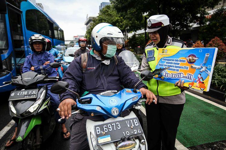 Petugas kepolisian dari direktorat lalu lintas (Ditlantas) Polda Metro Jaya menyosialisasikan penerapan sistem tilang elektronik atau electronic traffic law enforcement (ETLE) untuk kendaraan roda dua atau motor di Simpang Sarinah, Thamrin, Jakarta Pusat, Senin (3/2/2020). Untuk saat ini sistem ETLE untuk pengendara sepeda motor fokus pada penindakan tiga pelanggaran, yakni penggunaan helm, menerobos traffic light, dan melanggar marka jalan. Penerapan aturan tersebut telah resmi diberlakukan mulai Sabtu (1/2/2020).