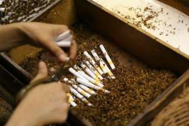 Seorang pekerja sedang memproses pembuatan rokok kretek.