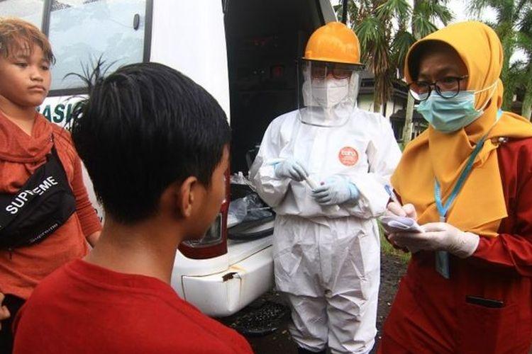 Dua petugas medis mencatat data remaja pesepeda yang terjaring razia kepatuhan penggunaan masker di Jalan Ahmad Yani, Pontianak, Kalimantan Barat, Senin (06/07).