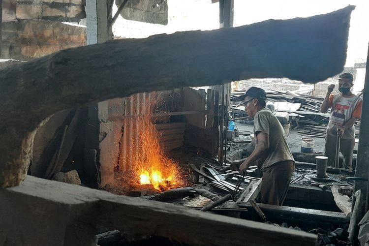Ilustrasi pandai besi yang memproduksi cangkul