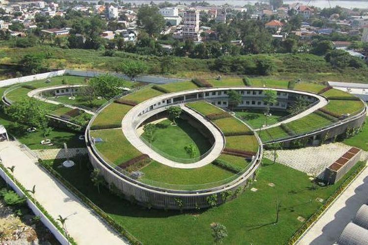 Gedung beratap hijau dan berbentuk cincin kembar tiga ini saling bertautan sehingga menciptakan tiga halaman bermain yang aman.