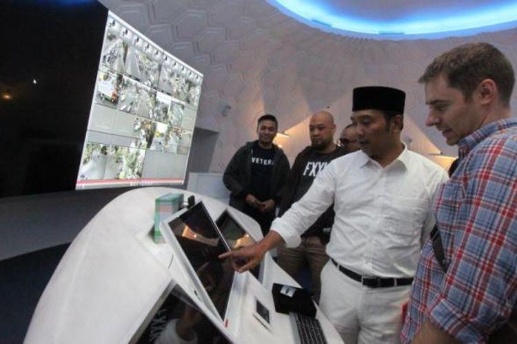 Wali Kota Bandung Ridwan Kamil saat memamerkan teknologi di Bandung Command Center kepada salah seoarang tamu asal luar negeri.