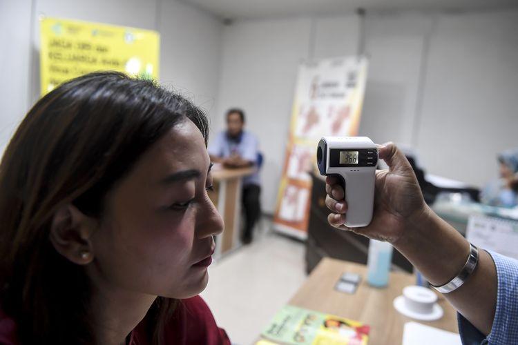 Seorang  petugas Pos Pemantauan virus Covid-19 memeriksa suhu seorang jurnalis di RSPI Prof. Dr. Sulianti Saroso, Sunter, Jakarta Utara, Rabu (4/3/2020). Pos pemantauan tersebut dibuka untuk masyarakat yang ingin berkonsultasi apabila mengalami gejala terjangkit virus Covid-19.