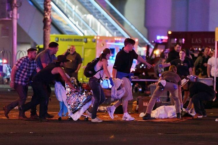 Korban dibawa ke tempat aman setelah terjadi penembakan massal di festival musik country di Las Vegas, Nevada, Minggu (1/10/2017). Seorang pria bersenjata melepaskan serentetan tembakan di festival musik di Las Vegas hingga menewaskan lebih dari 20 orang. Polisi telah menembak mati seorang tersangka.