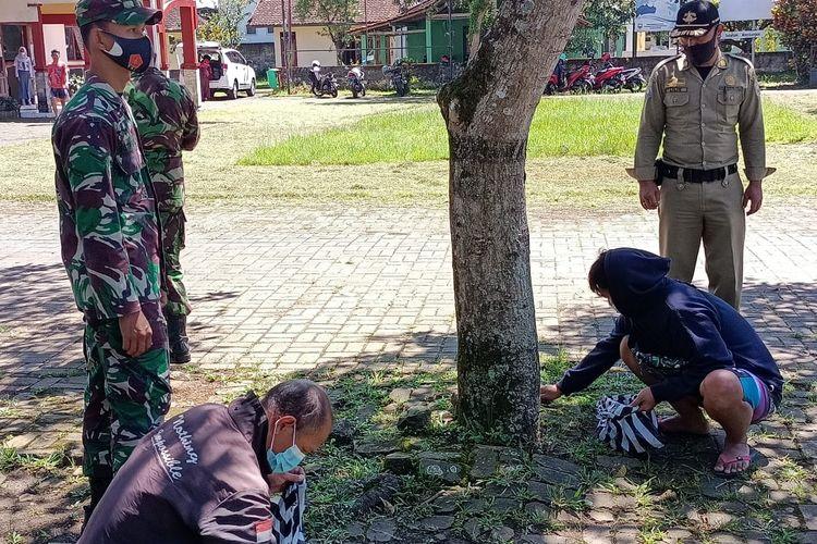 Pelanggar protokol kesehatan membersihkan halaman kantor Kecamatan Pabelan.