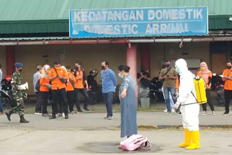 Petugas menyemprotkan disinfektan kepada TKI yang baru tiba di Lanud Soewondo pada Jumat (10/4/2020). Sebanyak 120 tenaga kerja Indonesia (TKI) gelombang ketiga yang mendarat di Bandara Internasional Kuala Namu pada Jumat (10/4/2020) pagi tadi dibawa ke eks Bandara Polonia Medan yang kini menjadi Lanud Soewondo.