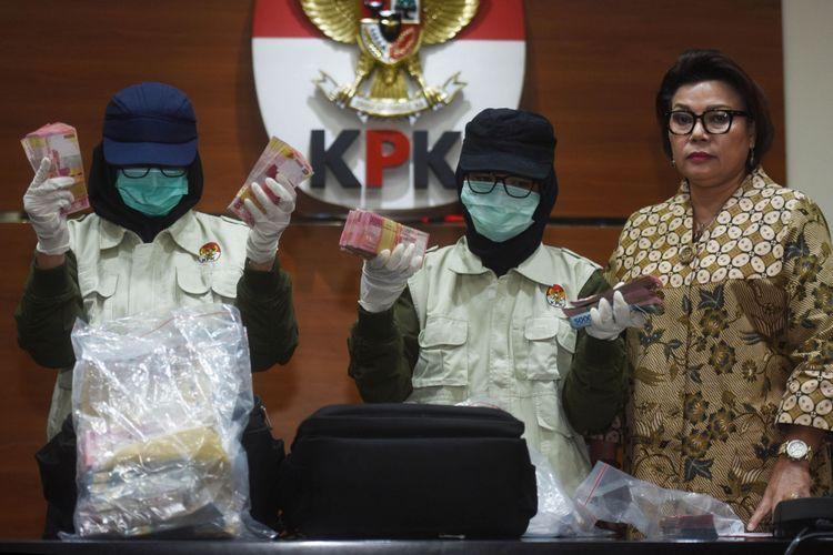 Dua petugas disaksikan Wakil Ketua KPK Basaria Panjaitan (kanan) menunjukkan barang bukti uang yang diamankan dari operasi tangkap tangan (OTT) Nganjuk, di Jakarta, Kamis (26/10). KPK menetapkan lima orang tersangka, termasuk Bupati Nganjuk Taufiqurrahman, serta menyita barang bukti uang sebesar Rp298 juta yang diduga merupakan uang suap jual beli jabatan di Kabupaten Nganjuk. ANTARA FOTO/Akbar Nugroho Gumay/kye/17