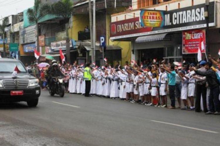 Para pelajar menunggu di jalan yang dilewati rombongan presiden sekitar dua jam ditengah rintih hujan