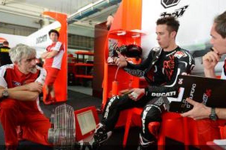 Pebalap Ducati Andrea Dovizioso (kanan) berdiskusi dengan kru tim saat menjalani sesi uji coba pramusim MotoGP 2014 di Sirkuit Sepang, Kamis (27/2/2014).