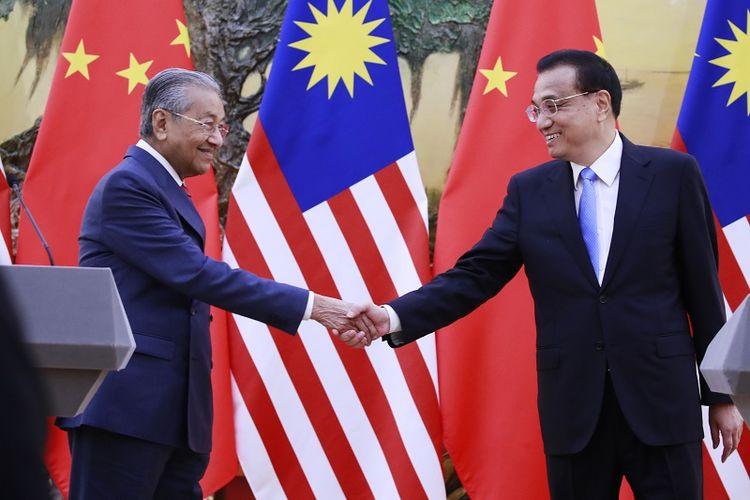 PM Malaysia Mahathir Mohamad menjabat tangan PM China Le Keqiang usai menggelar jumpa pers di Beijing, Senin (20/8/2018).