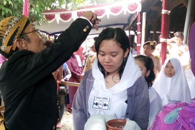Seorang peserta ruwatan (Sukerta) mengikuti prosesi potong rambut saat acara ruwatan massal di Pendopo Notobratan di Desa Kadilangu, Kabupaten Demak,  Jateng,  Minggu (23/4/2017).