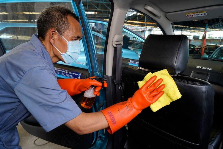 Ilustrasi petugas membersihkan taksi