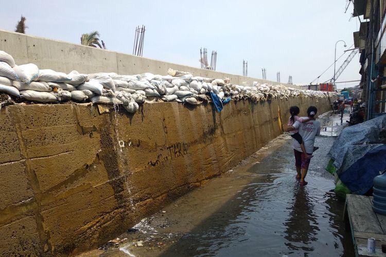 Warga melewati genangan air dari rembesan air laut yang menembus tanggul karung pasir di Muara Baru, Penjaringan, Jakata Utara, Rabu, (3/1/2018)