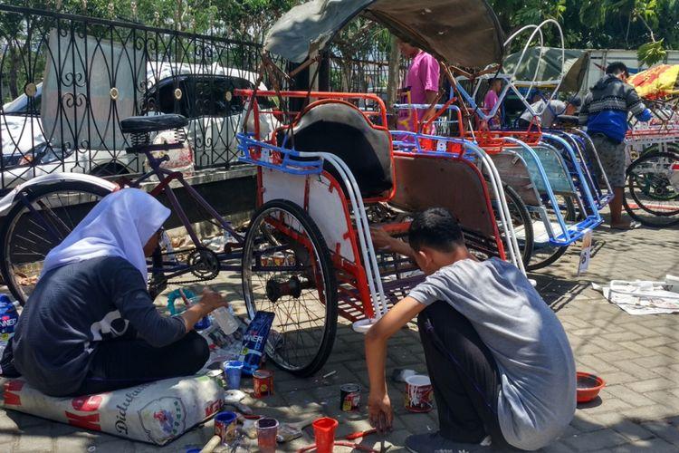 Salah satu tim pelajar tengah mengecat becak dalam rangka memeriahkan hari sumpah pemuda, yang diselenggarakan di halaman Kantor Polisi Resort Trenggalek Jawa Timur (28/10/2018)