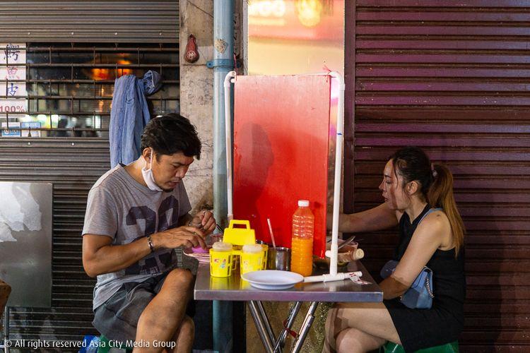 Terlihat dua orang yang sedang makan di meja yang sama di Yaowarat, Bangkok, tapi dibatasi dengan papan di antara mereka untuk menjaga jarak aman dalam masa lockdown di Bangkok, Thailand