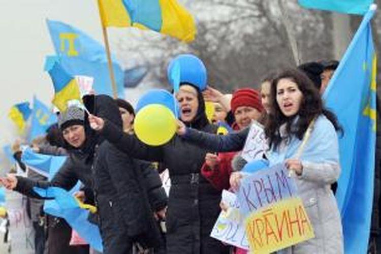 Para perempuan Tatar Crimea mengibarkan bendera Tatar dan Ukraina dalam sebuah unjuk rasa di kota Simferopol, Crimea, Sabtu (8/3/2014). Beberapa perempuan itu bahkan membawa spanduk dengan tulisan