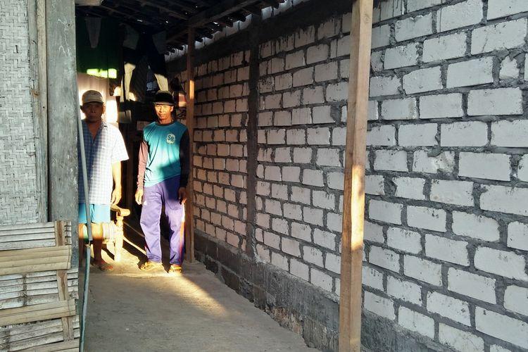 Kaslan (kiri) saat berada di depan rumah miliknya yang tertutup tembok bangunan tetangga di Desa Wudi, Kecamatan Sambeng, Lamongan, Minggu (1/9/2019).