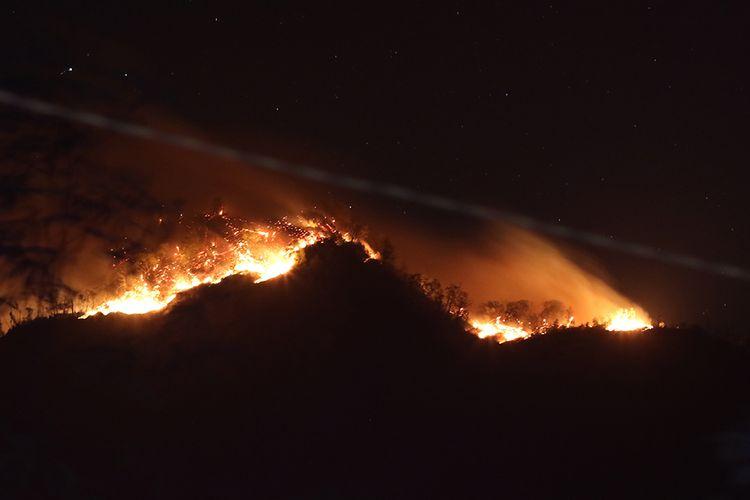 Kebakaran hutan Gunung Ranti terlihat dari Tawonan, Banyuwangi, Jawa Timur, Sabtu (19/10/2019). Kebakaran hutan tersebut menyebabkan jalur pendakian Gunung Ijen ditutup sementara serta diperkirakan empat pendaki masih terjebak di puncak.