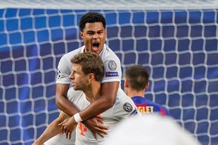 Pemain Bayern Muenchen, Serge Gnabry (atas) merayakan golnya bersama Thomas Mueller (bawah) setelah membobol gawang Barcelona di Stadion Da Luz, Portugal, Sabtu (15/8/2020).