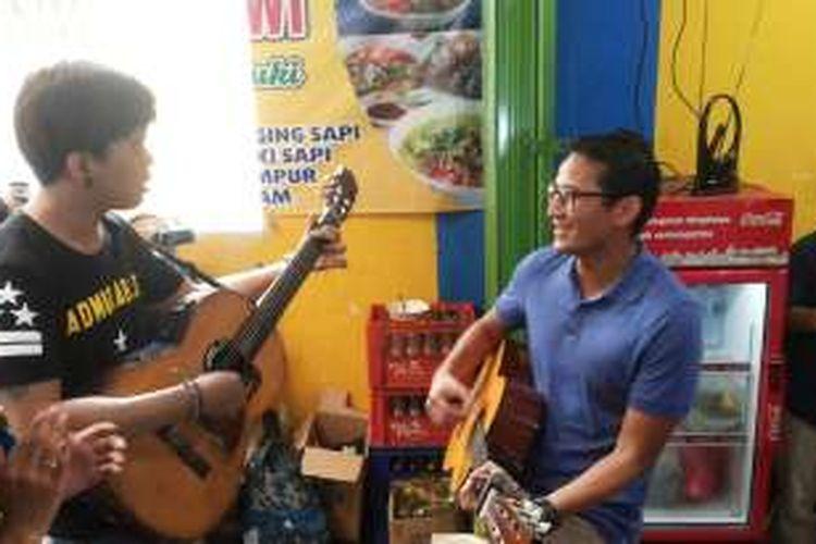 Calon wakil gubernur DKI Jakarta nomor tiga, Sandiaga Uno saat berduet bermain gitar dan bernyanyi dengan salah seorang pengamen di kawasan Rawasari Selatan, Cempaka Putih, Jakarta Pusat, Rabu (30/11/2016).