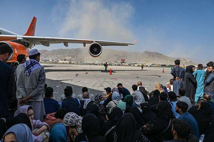 Orang-orang menunggu untuk dapat diberangkatkan dengan pesawat saat mereka berebut untuk melarikan diri ke luar negeri, di Bandara Kabul, Afghanistan, Senin (16/8/2021). Bandara Kabul dilanda kekacauan ketika ribuan orang mencoba melarikan diri dari Taliban yang dilaporkan segera menguasai penuh Afghanistan.