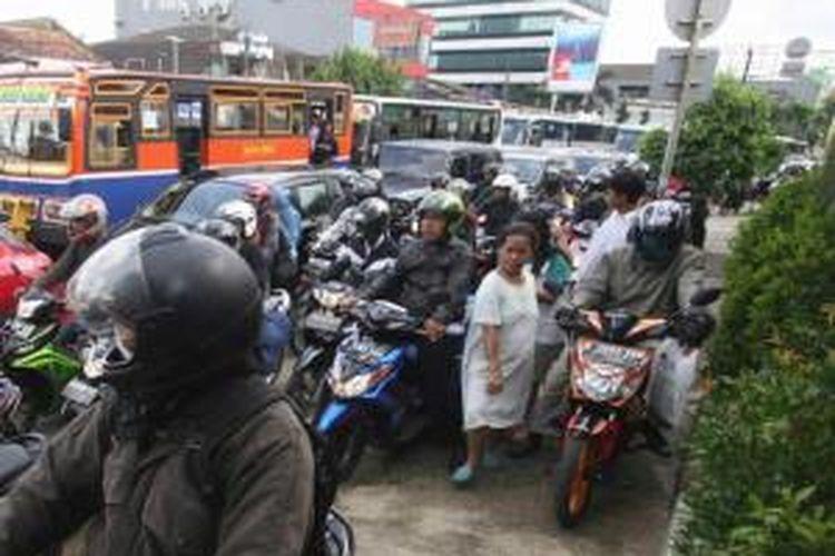 Pejalan kaki mencari jalan di antara sepeda motor yang memenuhi jalan hingga ke trotorar di Jalan Mampang Prapatan, Jakarta, Selasa (3/4/2012). Karena macet, sepeda motor kerap mengambil jatah trotoar yang menjadi tempat melintas pejalan kaki.