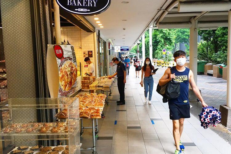 Seorang warga pria Singapura yang memakai masker terlihat berjalan di depan toko roti DJ Bakery di Tanjong Pagar Plaza, Rabu siang (21/10/2020). Singapura dijadwalkan akan memasuki Fase 3 atau New Normal pada bulan Desember 2020