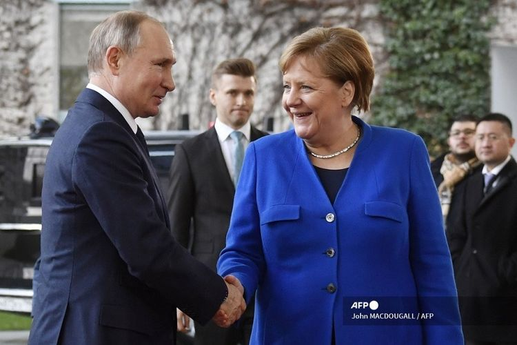 Ilustrasi Presiden Rusia dan Kanselir Jerman.  Kanselir Jerman Angela Merkel berjabat tangan dengan Presiden Rusia Vladimir Putin pada saat kedatangannya untuk menghadiri KTT Perdamaian di Libya di Kanselir di Berlin pada 19 Januari 2020.