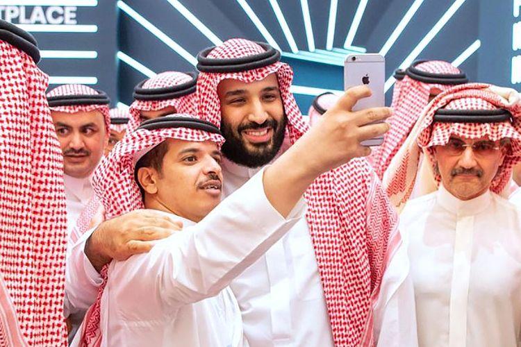 Dalam foto yang dirilis pada Selasa (23/10/2018), putra mahkota Arab Saudi Pangeran Mohammed bin Salman melakukan selfie dengan seorang pria di konferensi Inisiatif Investasi Masa Depan (FII) di Riyadh. Di sebelah MBS nampak miliarder Pangeran Al-Walid bin Talal, yang pernah ditangkap dalam operasi pemberantasan korupsi tahun lalu.