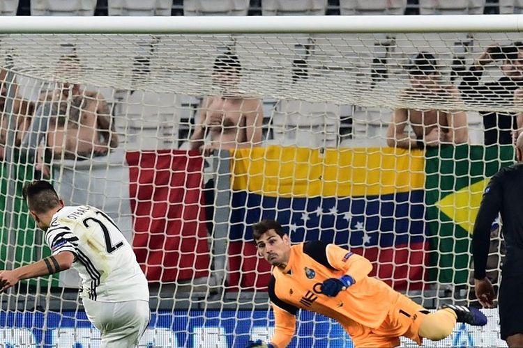 Penyerang Juventus dari Argentina Paulo Dybala (kiri) mencetak penalti melawan kiper Spanyol Porto, Iker Casillas selama pertandingan sepak bola Liga Champions UEFA Juventus vs FC Porto pada 14 Maret 2017 di stadion Juventus di Turin.