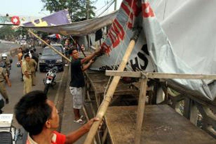 Pedagang kaki lima (PKL) membongkar dan memindahkan barang dagangannya saat petugas Satpol PP menertibkan mereka di Pasar Mainan Gembrong, Jakarta Timur, Rabu (14/8/2013). Petugas Satpol PP dibantu Polisi dan TNI menertibkan sepanjang Jalan Jatinegara hingga Stasiun dan Pasar Gembrong dari PKL yang membuka lapak hingga badan jalan yang menyebabkan kemacetan.