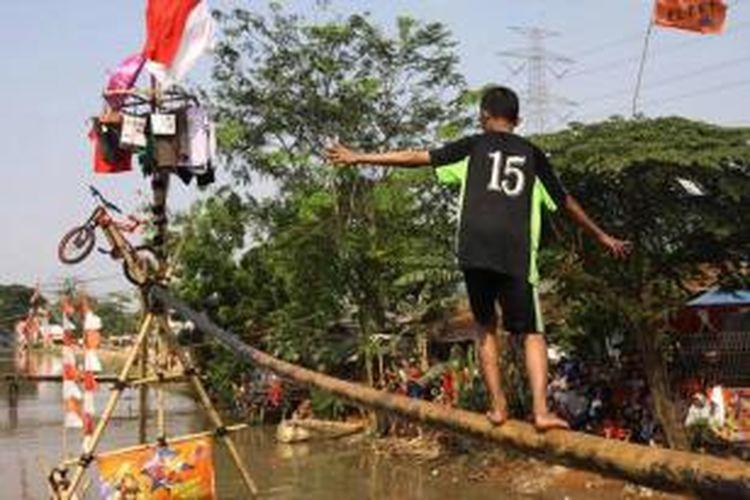 Peserta berusaha melewati batang pohon pinang yang telah diolesi oli untuk mengambil hadiah, di Kalimalang, Jakarta Timur, Senin (17/8/2015). Selain lomba titian pinang, juga diadakan lomba gebuk bantal dan juga lomba panjat pinang.