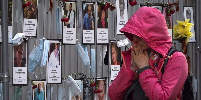 Foto ini diambil pada Rabu, 20 Mei 2020, tampak seorang wanita bereaksi ketika dia berjalan melewati potret pekerja medis Saint Petersburg yang meninggal akibat terinfeksi virus corona selama melakukan pekerjaan mereka.