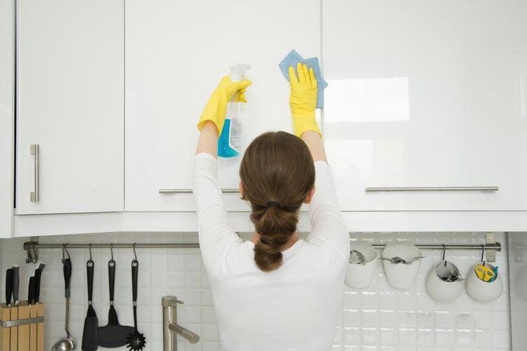 Membersihkan bagian lemari dapur.