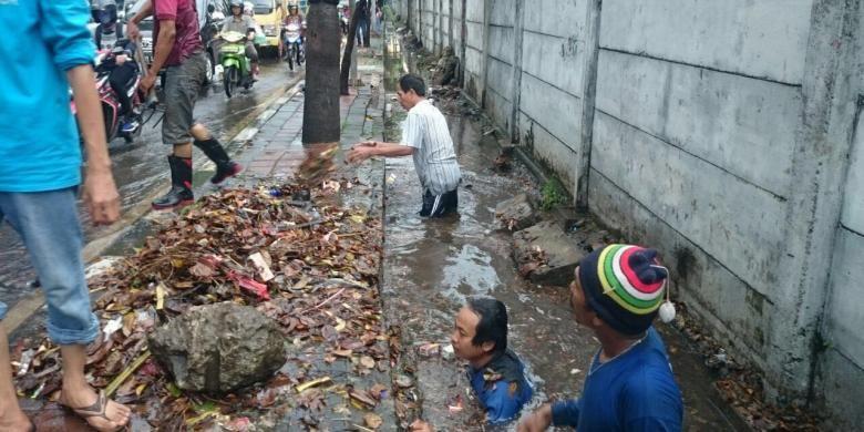 Pasukan Biru dari Dinas Tata Air DKI mengangkat sampah yang menyumbat saluran air di Jalan DI Panjaitan dan menimbulkan genangan sore ini, Selasa (1/11/2016)