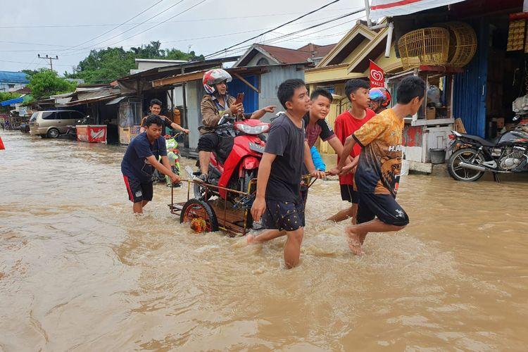 Genangan banjir di Jalan Gerilya, Samarinda. Warga membantu pengendara yang terjebak banjir, Jumat (13/12/2019).