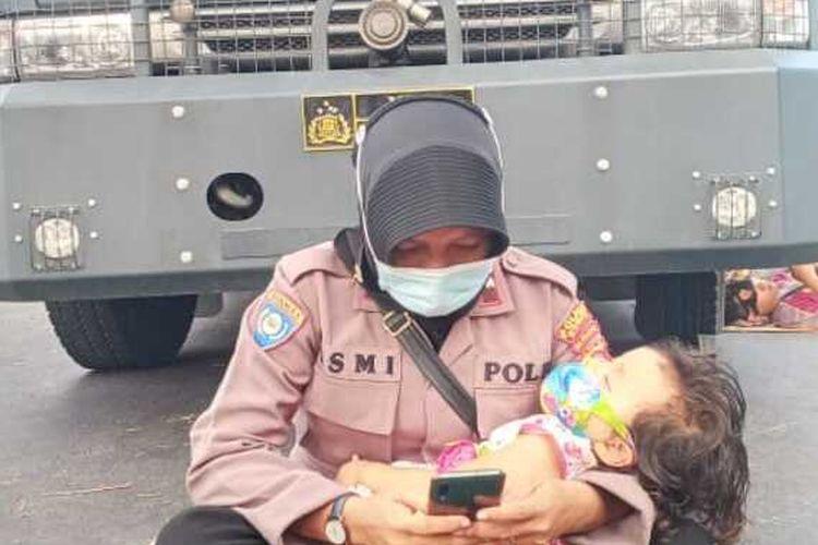 Foto Aipda Ismi, Polwan yang amankan sengketa Pilkada sambil memangku anaknya yang sedang tidur.