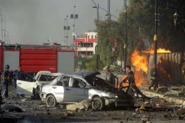 Tim tanggap darurat Irak memeriksa mobil-mobil yang hancur akibat serangan bom di sebuah gedung yang sedang dibangun di kota Kirkuk yang dikuasai etnis Kurdi, Sabu (23/8/2014). Tiga bom mobil yang nyaris bersamaan meledak di kota yang sedang diperebutkan di Irak utara ini.