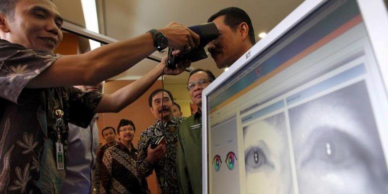 Petugas memindai iris mata Menteri Dalam Negeri Gamawan Fauzi untuk mencari data e-KTP miliknya di Kementerian Dalam Negeri, Jakarta Pusat, Kamis (8/11/2012). Mendagri menyatakan telah berhasil memenuhi target perekaman e-KTP dengan target 172.015.400 wajib KTP lebih cepat 55 hari daripada tenggat waktu yang ditentukan yaitu 31 Desember 2012.