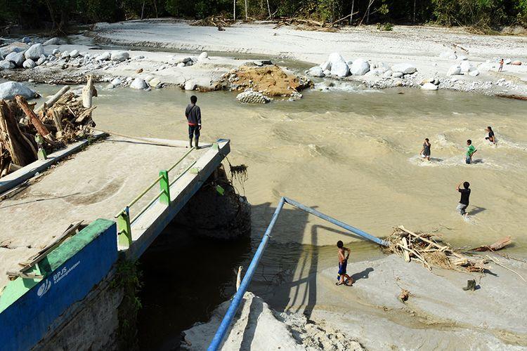 Pengungsi menyeberangi sungai di Desa Kamiri Masamba, Kabupaten Luwu Utara, Sulawesi Selatan, Selasa (21/7/2020). Warga di daerah tersebut terpaksa menyeberangi sungai untuk mengambil bantuan karena jembatan penghubung desa mereka terputus akibat diterjang banding bandang.