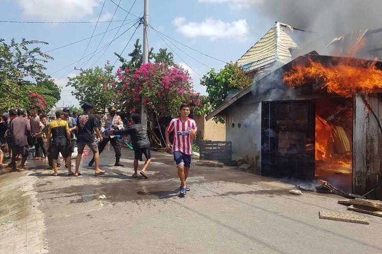 Petugas pemadaman dibantu polisi dan warga melakukan upaya pemadaman dalam peristiwa kebakaran yang menghanguskan 25 rumah di Kecamatan Pemulutan Ogan Ilir